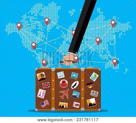 Travel Suitcase With Stickers Of Countrys And Citys All Over The World In Hand. World Map With Trave