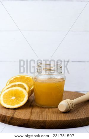 Honey Jar And Lemon Slices On A Wooden Board White Background