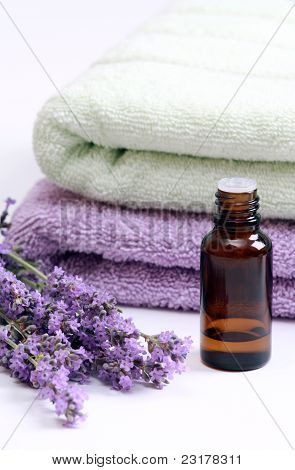 Aromatherapy oil and lavender flowers against terry towels poster
