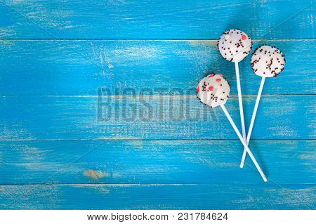 Holiday Treats. Cake Pops. Biscuit Cakes In White Chocolate Glaze On A Bright Blue Wooden Background