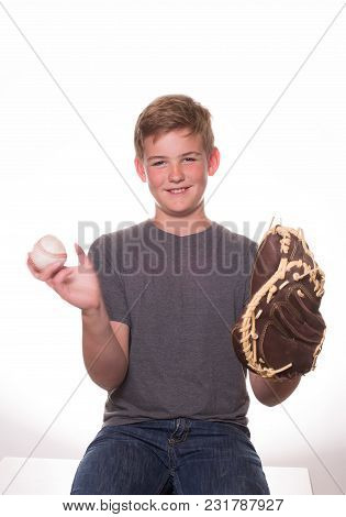 Teenage Boy Tossing A Baseball Into His Glove.
