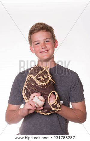 Boy With Smile On His Face Wearing A Baseball Glove And Holding A Ball. White Background.