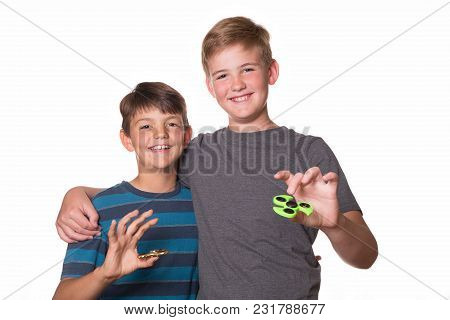 Two Boys/brothers Playing With Fidget Spinners On White Background.