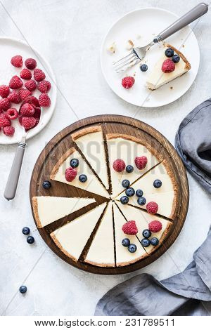 Classic New York Cheesecake With Fresh Raspberries And Blueberries On White Concrete Background, Top