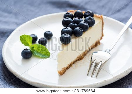 Slice Of Cheesecake With Blueberries And Mint Leaf On White Plate, Closeup View, Selective Focus