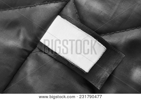 Blank Clothes Label On Black Textile Background Closeup