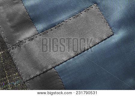 Blank Black Clothes Label On Textile Background Closeup