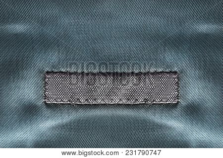 Blank Textile Clothes Label On Blue Satin Background