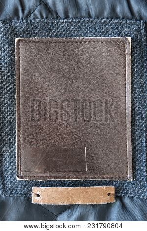 Blank Leather Clothes Label On Blue Textile Background Closeup