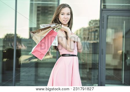 A Smiling Young Woman Throws Paper Bags On Her Shoulder. Walking After Shopping. Standing Against Th