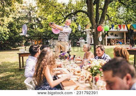 Family Celebration Outside In The Backyard. Big Garden Party. Grandfather Taking Selfie With A Camer