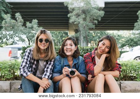 Group Of Young Asian Women Sitting Along The Street Enjoying Their City Lifestyle In A Morning Of A