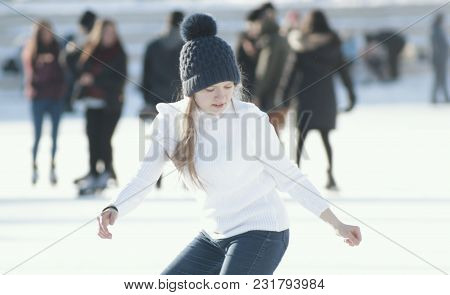 Teen Girl Skillfully Skating On Outdoor Public Ice Rink, Youth Pastime And Rest