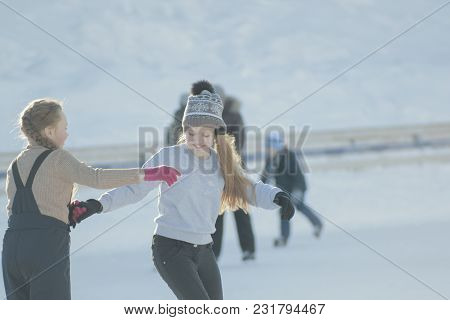 Two Teen Girlfriends Learning To Skate And Having Fun At The Rink, Youth Pastime And Rest
