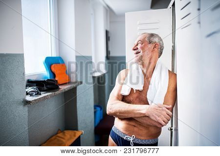 Senior Man Standing By The Lockers In An Indoor Swimming Pool. Active Pensioner Enjoying Sport.