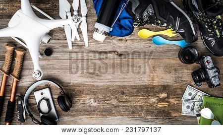 Objects for adventure trip - quadcopter, trekking pole, vintage camera, trekking shoes, money and passport on rustic wooden background. Tourist lifestyle poster
