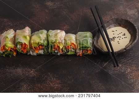 Fresh Handmade Vegan Asian Spring Rolls With Rice Noodles, Avocado, Carrots And Tahini Dressing On D