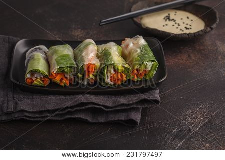Fresh Handmade Vegan Asian Spring Rolls With Rice Noodles, Avocado, Carrots And Tahini Dressing On B