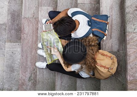 Two Young Tourists With Smartphone And Map In The Old Town. Teenagers Sitting On The Stairs. Top Vie