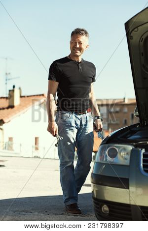 Man with wrench and other tools standing near car.  Man repairing the engine in the car. Auto repair. Auto Mechanic.