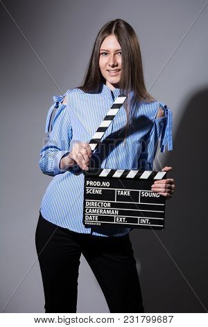 Smiling Young Woman With Movie Clapper