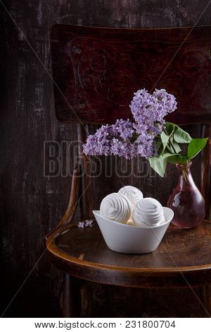 Bowl Of White Zephyr Marshmallows And Bouquet Of Lilac Flowers On Old Vintage Chair.  Still Life On