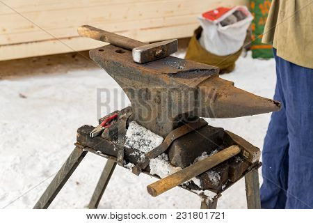 Blacksmith Manually Forging The Molten Metal On The Anvil Outdoors