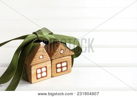 Pair Of Wooden Houses Together Tied With A Green Bow / Gift Offer Two For The Price Of One