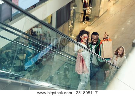High Angle View Of Shoppers Riding Escalator At Mall
