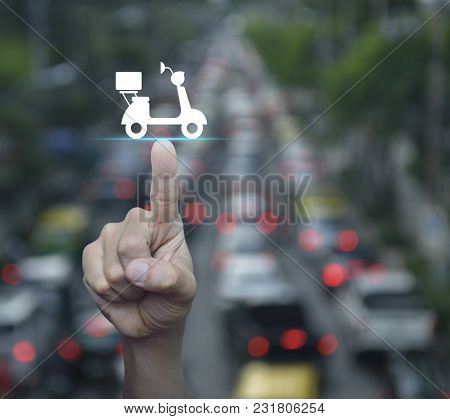 Hand Pressing Motor Bike Icon Over Blur Of Rush Hour With Cars And Road, Business Delivery Service C