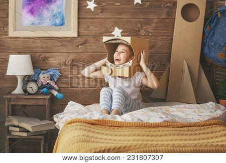 Child girl in astronaut costume with toy rocket playing and dreaming of becoming a spacemen. Portrait of funny kid in the bedroom.