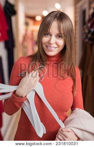 Young smiling girl with hangers in the store