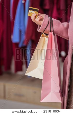 Young girl with a credit card and shopping bags indoors