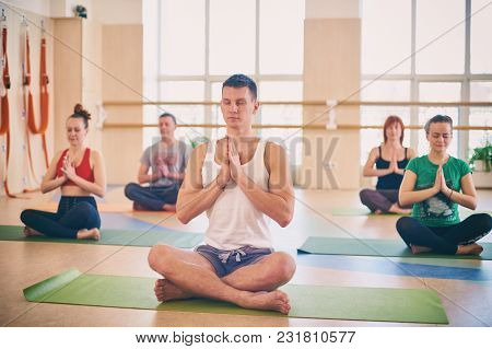 Group Of Young Sporty People Practicing Yoga Lesson With Instructor, Sitting In Padmasana Exercise,