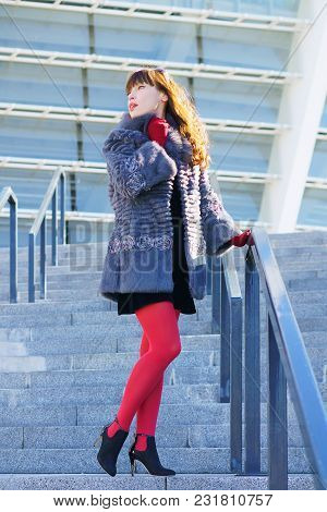 Sexy Woman In A Black Dress, Red Tights And A Fur Coat Standing On Stairs