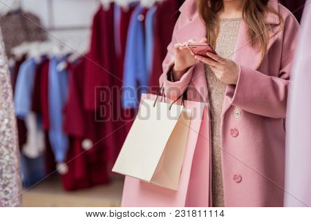 Young girl with shopping bags indoors