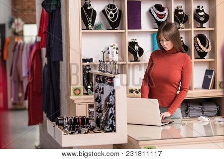 Young cashier at the counter in the store
