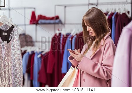 Young girl with a phone in the store