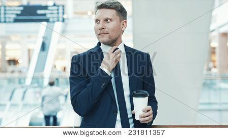 Young businessman with coffee in the store