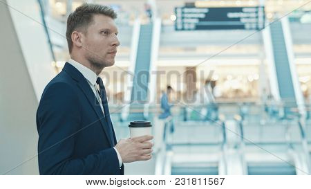 Young businessman with coffee indoors