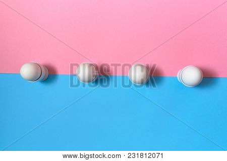 White Eggs Standing On Egg Cup On Blue And Pink Pastel Background, Copy Space. Row Boiled Eggs In St