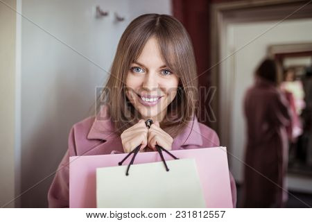 Happy girl with shopping bags in dressing room