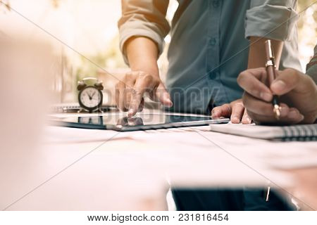 Business People Examining Financial Reports And Analyzing Business Growth With Pointing On Digital T