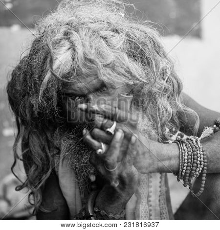 VARANASI, INDIA - MAR 16, 2018: Hindu sadhu smoking ganja, marihuana with chillum  on the ghats of the Ganges river. According to legends, the city was founded by God Shiva about 5000 years ago.