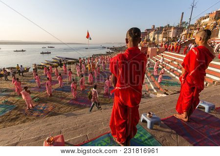 VARANASI, INDIA - MAR 18, 2018: Young hindu monks conduct a ceremony to meet the dawn on the banks of the Ganges, and raise the Indian flag. Varanasi is one of the 7 sacred cities of Hinduism.