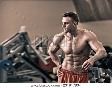 Young Healthy Man With Perfect Muscular Body In The Gym, The Image Was Desaturated Ang Toned