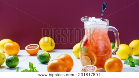 Summer drink and citrus fruits with space for text. Jug of citrus lemonade