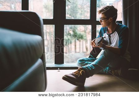 Yong Guy Plays On Guitar Sitting On The Floor In Living Room