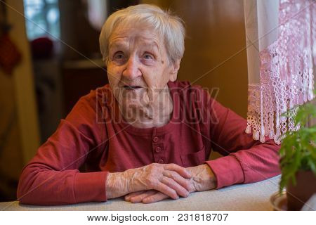 Elderly senior woman sitting at the table in home.
