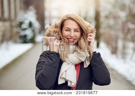 Attractive Stylish Smiling Blond Woman In A Misty Street In Winter Wearing A Warm Overcoat And Handb
